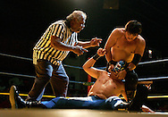 Halcon de Oro tries to remove Temblor's mask during a fight at the Tejano Saloon as referee Baru warns him.  Removing an opponent's mask means disqualification.