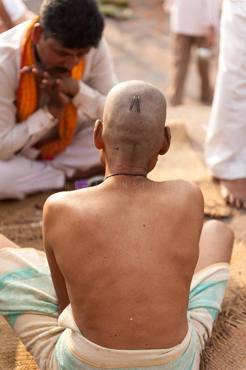 A man in mourning consults a pandit (priest) at Dashashwamedh ghat, Varanasi, India. Photo © robertvansluis.com