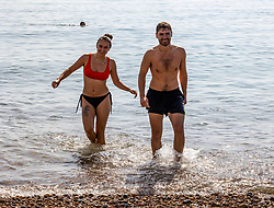 Licensed to London News Pictures. 06/09/2021. Brighton, UK. Swimmers Oscar Stelzer-Hiller 22 and Ella Powles cool off with a splash in the sea at Brighton Beach, East Sussex as weather forecaster predict a mini-heatwave for September this week with temperatures hitting over 29c tomorrow. Photo credit: Alex Lentati/LNP