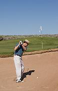 Vertical of golfer in sand trap