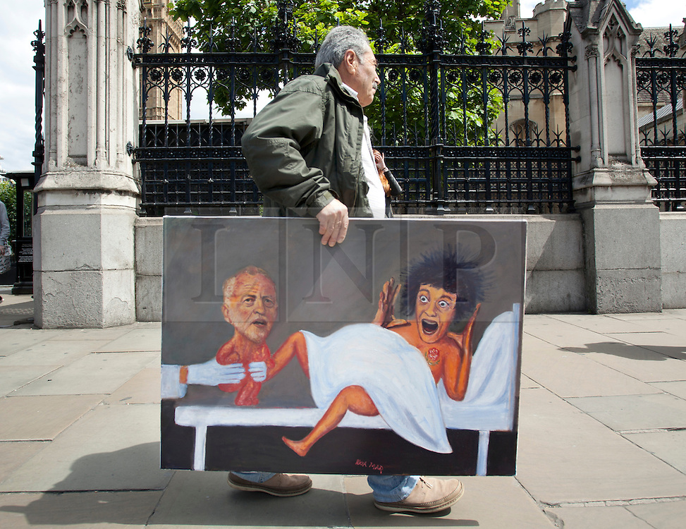 """© Licensed to London News Pictures. 29/07/2015. London, UK.  27/04/2015. London, UK. Political artist Kaya Mar poses outside Westminster Palace, central London, with his latest satirical painting portraying Labour leadership candidate Jeremy Corbyn as the newborn baby of """"mother Labour"""" Photo credit : LNP"""