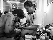 """07 MARCH 2015 - NAKHON CHAI SI, NAKHON PATHOM, THAILAND: A man who got a spiritual Sak Yant tattoo (left) prays with the tattoo master at the Wat Bang Phra tattoo festival. Wat Bang Phra is the best known """"Sak Yant"""" tattoo temple in Thailand. It's located in Nakhon Pathom province, about 40 miles from Bangkok. The tattoos are given with hollow stainless steel needles and are thought to possess magical powers of protection. The tattoos, which are given by Buddhist monks, are popular with soldiers, policeman and gangsters, people who generally live in harm's way. The tattoo must be activated to remain powerful and the annual Wai Khru Ceremony (tattoo festival) at the temple draws thousands of devotees who come to the temple to activate or renew the tattoos. People go into trance like states and then assume the personality of their tattoo, so people with tiger tattoos assume the personality of a tiger, people with monkey tattoos take on the personality of a monkey and so on. In recent years the tattoo festival has become popular with tourists who make the trip to Nakorn Pathom province to see a side of """"exotic"""" Thailand.   PHOTO BY JACK KURTZ"""