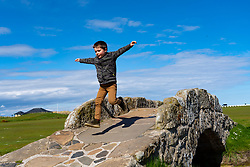 St Andrews, Scotland, UK. 4 May 2020.  The famous Old Course at St Andrews is closed due to the coronavirus lockdown. Locals are making the most of the closed golf course by using it as a park for they daily exercise. Pictured. 4 year old Harvey from St Andrews makes the most of the course closure by playing on the famous Swilken Bridge on the eighteenth hole. Iain Masterton/Alamy Live News