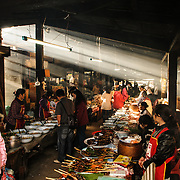 Vendors at the large undercover morning market in Phonsavan in northeast Laos sell a wide range of freshly cooked food and local cuisine, including grilled sparrow, pork, chicken, insects, and dog. The people of the region are predominantly of Hmong ethnicity.