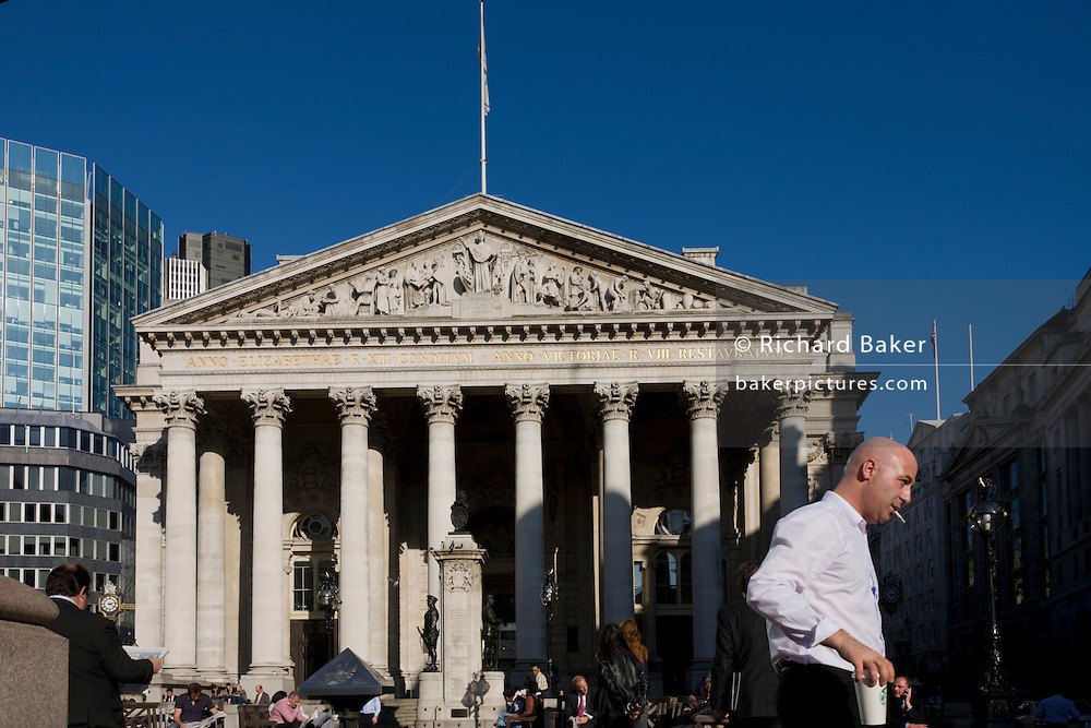 While smoking a cigarette, a businessman walks away with his Starbucks coffee after a mid-afternoon break beneath the Romanesque columns of the Royal Exchange in Bank triangle in the City of London. The tall and solid Corinthian pillars of the 3rd Royal Exchange built in 1842 by Sir William Tite. Looking upwards towards a memorial that commemorates the dead from the First World War of 1914-18 between the converging pillars of the Cornhill Exchange building and beyond, to the famous Bank of England in the City Of London, the financial district, otherwise known as the Square Mile.