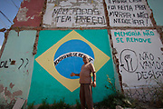 Augusto Periera outside his home before it is demolished, in front of a Brazil flag that reading memory cannot be removed. His house is one of the last standing of the original homes, and was demolished today. Vila Autodromo favela, in the west zone of Rio, is in direct site of the Rio 2016 Olympic park. There has been an ongoing struggle between residents and the City Government of Eduardo Paes. After a long battle, 20 families who held on were allowed to stay, on the provision that they moved into houses constructed by the state, in the same style as the public housing programme.