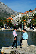 Two children (5 years old, 9 years old) on stone jetty with Korcula old town in background. Island of Korcula, Croatia