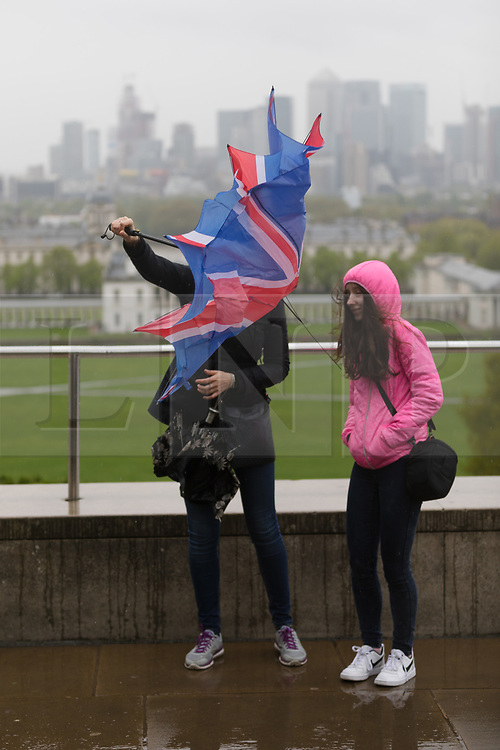 © Licensed to London News Pictures. 30/04/2018. London, UK. A woman struggles with umbrella in the wind during wet and windy weather at the top of the hill in Greenwich Park in London. The capital has been experiencing heavy rain and windy weather today. Photo credit: Vickie Flores/LNP