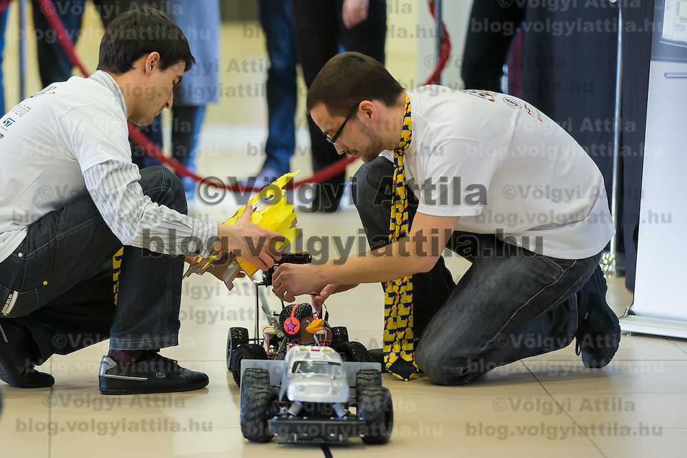 Competitors adjust their car during the RobonAut technical university race for self driving autonomous cars in Budapest, Hungary on January 10, 2015. ATTILA VOLGYI