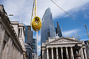 A coil of electrical wiring cables is above the heads of pedestriansnear Royal Exchange on Threadneedle Street - part of ongoing alterations to the highway during the Coronavirus pandemic in the City of London, the capital's financial district, on 30th July 2020, in London, England. SRL are the UK's only manufacturer to sell and hire traffic light equipment and their Urban64 product is the first, and only, permanent technology system to be designed uniquely for temporary installations in the U.K. The Urban64 design allows for simple and quick over-head installation, with the ability to replicate the technology provided by the preceding permanent system, and therefore maintaining traffic flow efficiency.