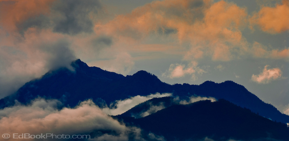 Clearing clouds from a rare summer storm cross Mt Jupiter in the Olympic Mountains as seen from the Kitsap Peninsula in Puget Sound, Washington, USA.