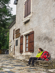 Woman hiker taking rest on a bank in front of an old building in the village of Gavarnie, France