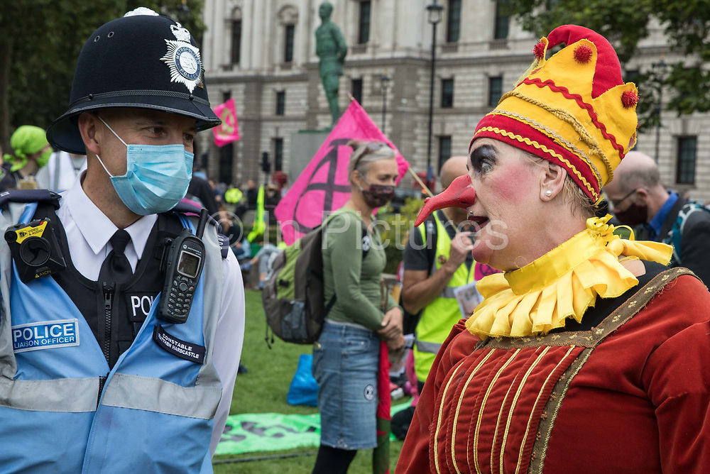 A Metropolitan Police liaison officer speaks to a jester from Extinction Rebellion at a 'Carnival of Corruption' protest against the government's facilitation and funding of the fossil fuel industry on 3 September 2020 in London, United Kingdom. Extinction Rebellion activists are attending a series of September Rebellion protests around the UK to call on politicians to back the Climate and Ecological Emergency Bill CEE Bill which requires, among other measures, a serious plan to deal with the UK's share of emissions and to halt critical rises in global temperatures and for ordinary people to be involved in future environmental planning by means of a Citizens' Assembly.