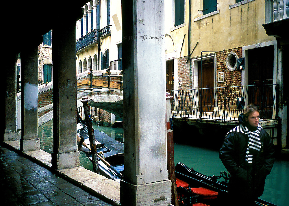 Walkway along a narrow canal in Venice; alongside, a gondola waits, its gondolier in his striped scarf stands at the bow looking straight ahead.  Close feeling of urban Venice.