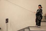 JAPAN, YOKOHAMA - 12 AUGUST 2012 - a woman wearing kimono is in the stairs of the concert room of the National Museaum of art [FR] Une femme portant un kimono noir est dans les escaliers menant à la salle de concert du musee national d'art de Yokohama