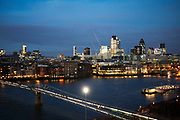 View towards the City of London across the River Thames. People cross the Millennium Bridge as the evening light fades and the lights in offices come on.