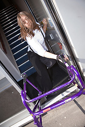 Young woman with walking frame leaving work,