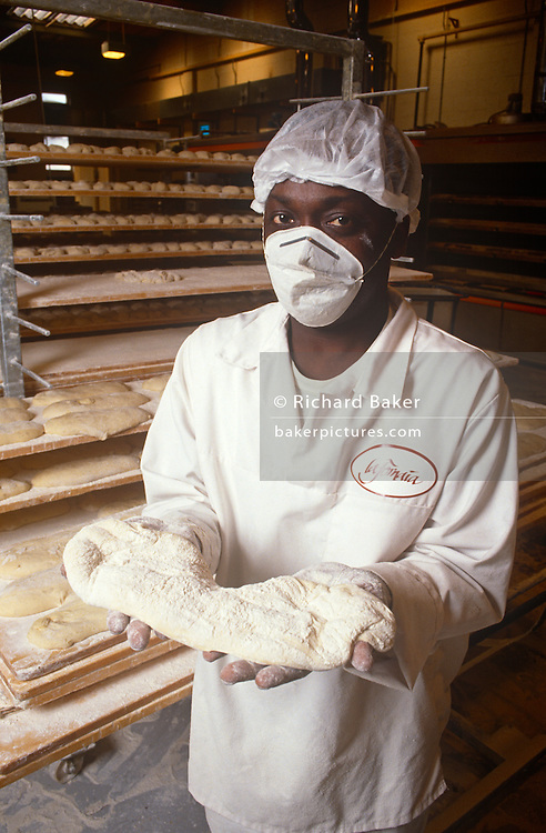 "A portrait of a baker holding yet to be baked dough for Ciabatta bread. Standing by trays of ready to bake loaves, the man is of African or afro-Caribbean origin, clearly made out in the white of his uniform and mix, his white baker's uniform's sleeves also spattered with flour. Ciabatta (literally ""carpet slipper"") is an Italian white bread made with wheat flour and yeast. The loaf is somewhat elongated, broad and flattish. Its name is the Italian word for slipper. There are many variations of ciabatta. Ciabatta in its modern form was developed in 1982. Since the late 1990s it has been popular across Europe and in the United States, and is widely used as sandwich bread."