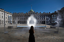 © Licensed to London News Pictures. 25/06/2018. London, UK. Artist Mimi Son watches her creation entitled 'HALO' an art installation that uses 99 mirrors to track the sun and draw a circle of light in a mist of water. Created by Seoul-based experimental art studio Kimchi and Chips (founded by Mimi Son and Elliot Woods) the display runs until June 27th, 2018. Sunny weather has brought high temperatures to most of the UK. Photo credit: Peter Macdiarmid/LNP
