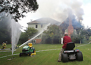 Homeowner Maynard Pritchett watches Albemarle County fire fighters from his riding mower work to extinguish a fire at his home late Tuesday afternoon on Balbion Drive in Albemarle County, Va. No one was injured in the fire that is believed to have started in a pantry area. Photo/The Daily Progress/Andrew Shurtleff