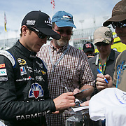 Driver Kasey Kahne signs autographs for fans in the garage area during the last practice session for the 57th Annual NASCAR Daytona 500 race at Daytona International Speedway on Saturday, February 21, 2015 in Daytona Beach, Florida.  (AP Photo/Alex Menendez)