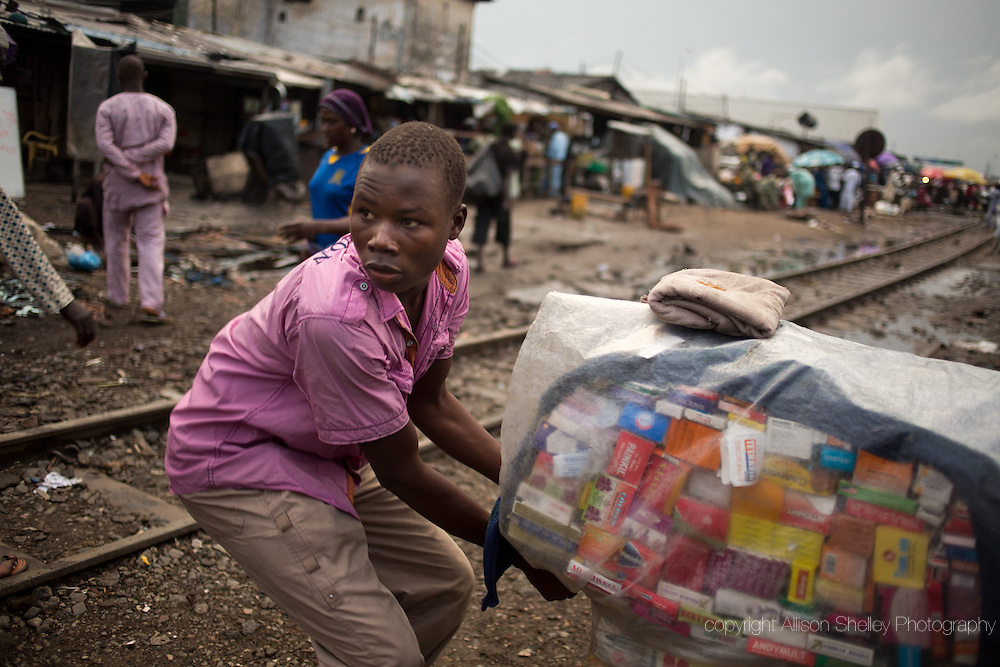 """A local """"hawker"""" sells drugs from a basket that he carries on his head, in the Badia neighborhood of Lagos, Nigeria, September 20, 2013. Wares include condoms, made-in-Nigeria herbal remedies and all manner of pills, sometimes including prescription-only drugs used for abortion. Public clinics are supposed to offer free condoms but are often out of stock."""