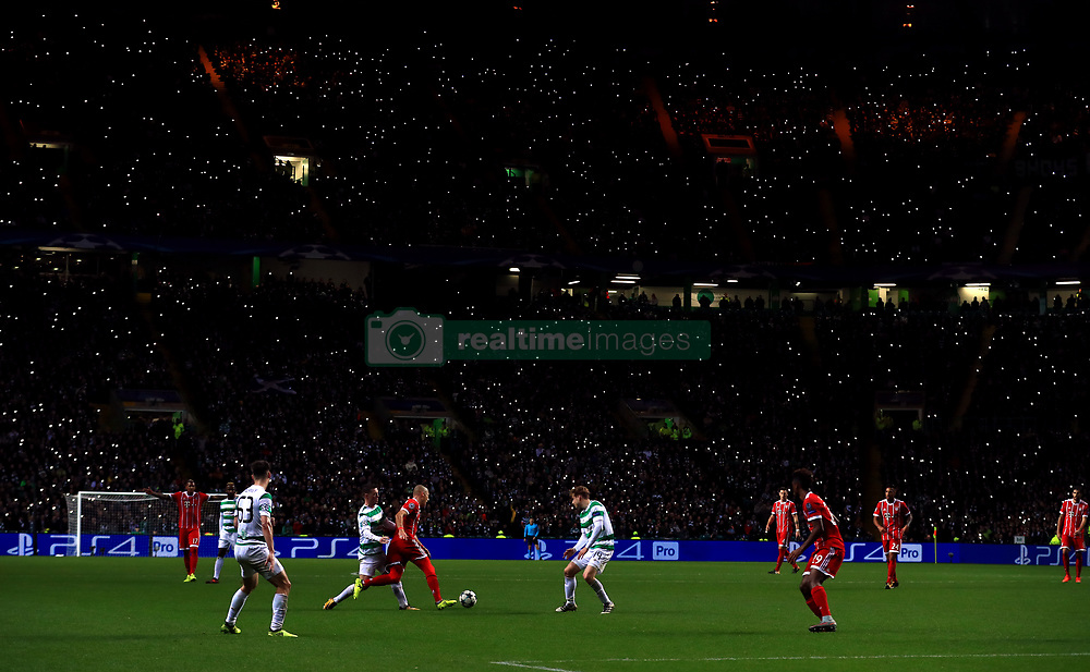 Fans in the stands hold up their phones with the torch lit as the action happens on the pitch