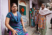 An Operation Asha counsellor sits outside a health clinic as Tuberculosis (TB) patients arrive in Tehkhand Slum, Delhi, India.  This clinic dispenses free TB medication provided by the government.  The treatment for TB is a minimum 6 month course of combination antibiotics that must been taken everyday, otherwise fatal drug resistance can develop. TB is an infectious disease and a huge public health issue often associated with poverty.  TB is completely curable, however TB rates are increasing and India suffers from the highest burden of TB in the world.