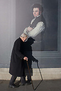 An elderly man with a stick (with his well-defined shadow) walks past the portrait by Francesco Goya of Don Tiburcio Pérez y Cuervo, the Architect, sponsored by Credit Suisse and advertised on a construction hoarding outside the National Portrait Gallery. Paintings by the Spanish romantic court artist are being exhibited inside the National Gallery next door and while a large grey hoarding is in place during works in Trafalgar Square, some of Goya's work is reproduced to viewers outside.