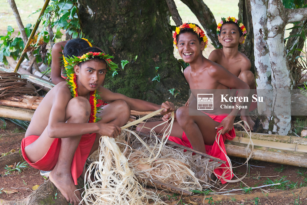 Boys using palm tree bark to make ropes, Yap Island, Federated States of Micronesia