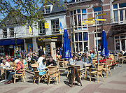 Outdoors cafe people sitting at tables and chairs, Den Burg, Texel, Netherlands,