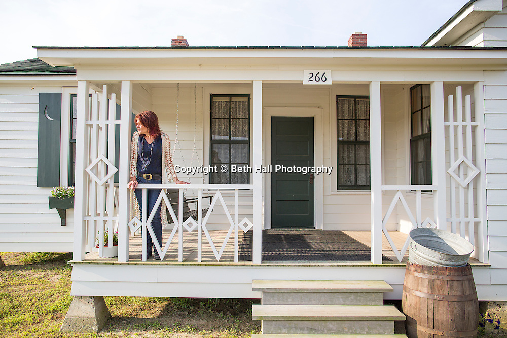 Rosanne Cash stands on the front porch of her father Johnny Cash's boyhood home on Saturday, August 16, 2014, in Dyess, Ark. The home was restored to it's appearance when the Cash family lived in it, from 1935-1954, and was part of The Dyess Colony that was created in 1934 as part of President Franklin D. Roosevelt's New Deal.<br /> <br /> Photo by Beth Hall
