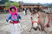 Mo Suo minority woman in traditional dress with her horse at Lugu Lake, in Yunnan, China. This is genuine traditional dress worn not for tourism, but as everyday dress. This is a poor run down area with little infrastructure such as roads, hotels or things tourists expect.