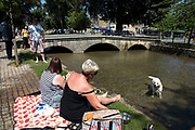 Dog enjoying the cool water at Bourton on the Water in The Cotswolds, United Kingdom. Bourton-on-the-Water is known for its picturesque High Street, flanked by long wide greens and the River Windrush that runs through them. The river is crossed by several low, arched stone bridges. These arched bridges have led to Bourton-on-the-Water being called the 'Venice of the Cotswolds'. Bourton-on-the-Water often has more visitors than residents during peak times of the tourist season. The Cotswolds is an area in south central England. The area is defined by the bedrock of limestone that is quarried for the golden coloured Cotswold stone. It contains unique features derived from the use of this mineral; the predominantly rural landscape contains stone-built villages and historical towns.