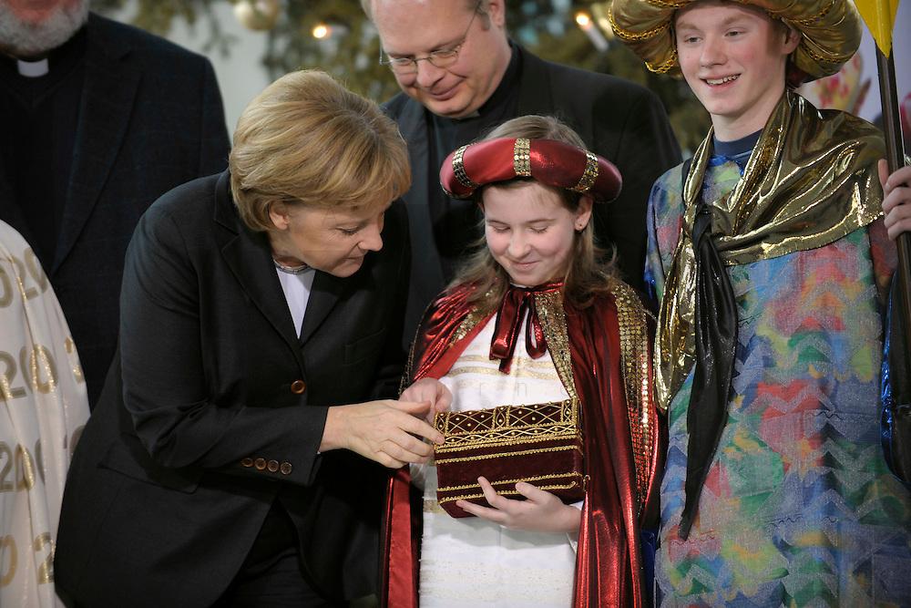 04 JUN 2008, BERLIN/GERMANY:<br /> Angela Merkel, CDU, Bundeskanzlerin, schaut einem der Heiligen drei Koenige in die Goldtruhe, waehrend dem Empfang der Sternsinger im Bundeskanzleramt<br /> IMAGE: 20080104-01-011<br /> KEYWORDS: Heilige drei Koenige, Heilige drei Könige, Kanzleramt