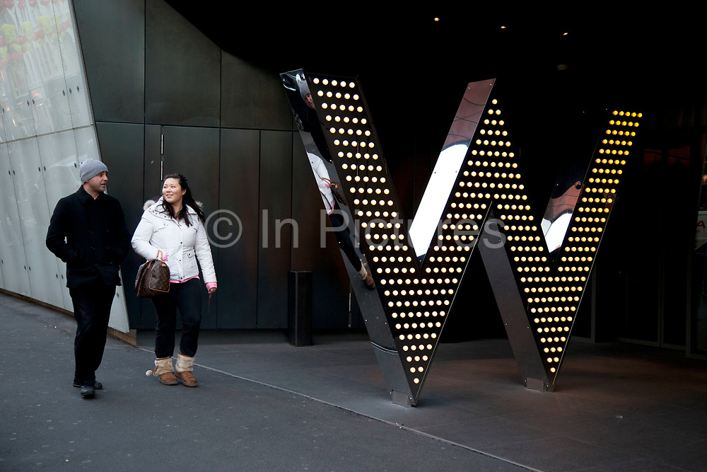 People passing the entrance to the W Hotel in central London. This hotel chain provides an exclusive chic and boutique experience for their customers.