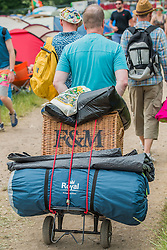 Some are posher than others. Arrivals face blistering heat as they struggle in with their kit. The 2015 Glastonbury Festival, Worthy Farm, Glastonbury.