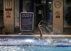 © Licensed to London News Pictures. 29/03/2021. London, UK. A swimmer passes a Covid-19 warning sign as he exercises at Hampton outdoor pool in south west London before dawn. The pool opened for the return to outdoor swimming at 4:45am. Covid regulations have changed today to allow gatherings up to six people outdoors. With sporting facilities, such as tennis,basketball courts and outdoor swimming pools allowed to reopen. Photo credit: Peter Macdiarmid/LNP