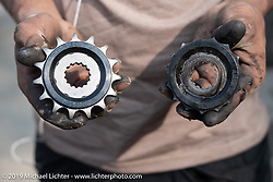 Muhammad Kurshid, Motorcycle Sherpa's Lead Mechanic (and master of roadside repairs) showing off the sprocket swap he is working on during our Ride to the Heavens motorcycle adventure in the Himalayas of Nepal. On the second day of riding, we went from Nuwakot to Pokhara. Tuesday, November 5, 2019. Photography ©2019 Michael Lichter.