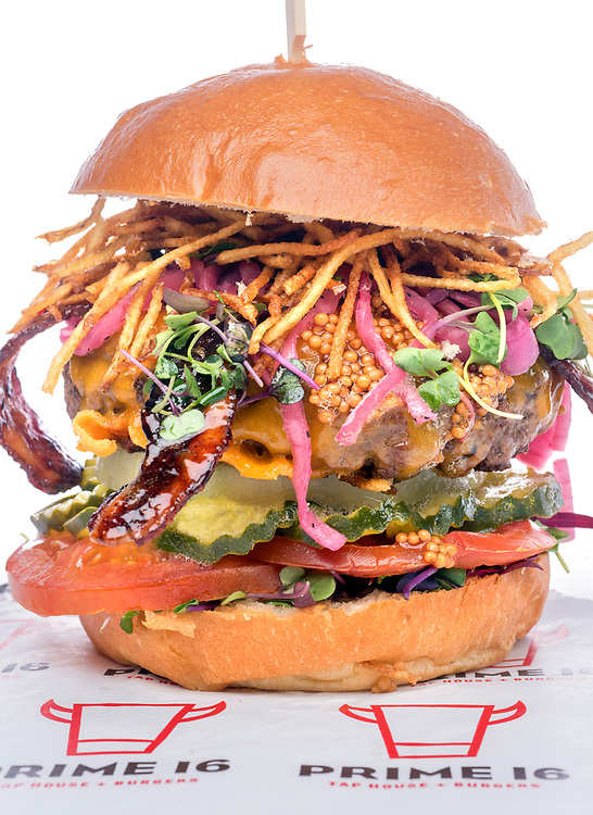 """Photo by Mara Lavitt<br /> New Haven, CT<br /> March 27, 2017<br /> Prime 16 (New Haven location) burgers. <br /> Prime 16 """"Elm City Crunch"""": Prime 16 signature beef patty, sriracha-glazed bacon, Wisconsin cheddar cheese, potato straws, pickled mustard seed, dill pickles, white onion, sliced tomato, and micro greens, all on a brioche bun."""