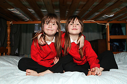 Twin sisters with their arms around each other; sitting on their bunk beds,