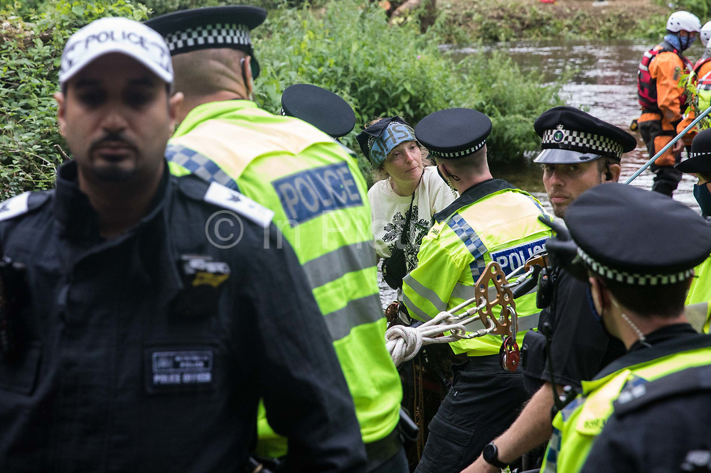 Police officers arrest Swan, an environmental activist from HS2 Rebellion who had been seeking to protect an ancient alder tree from destruction during works for the HS2 high-speed rail link, after she fell from a line which had been cut from the tree during a multi-force policing operation on 24th July 2020 in Denham, United Kingdom. Officers from the Metropolitan Police, Thames Valley Police, City of London Police and Hampshire Police attended to ensure the removal of the tree by HS2 despite protests from activists.