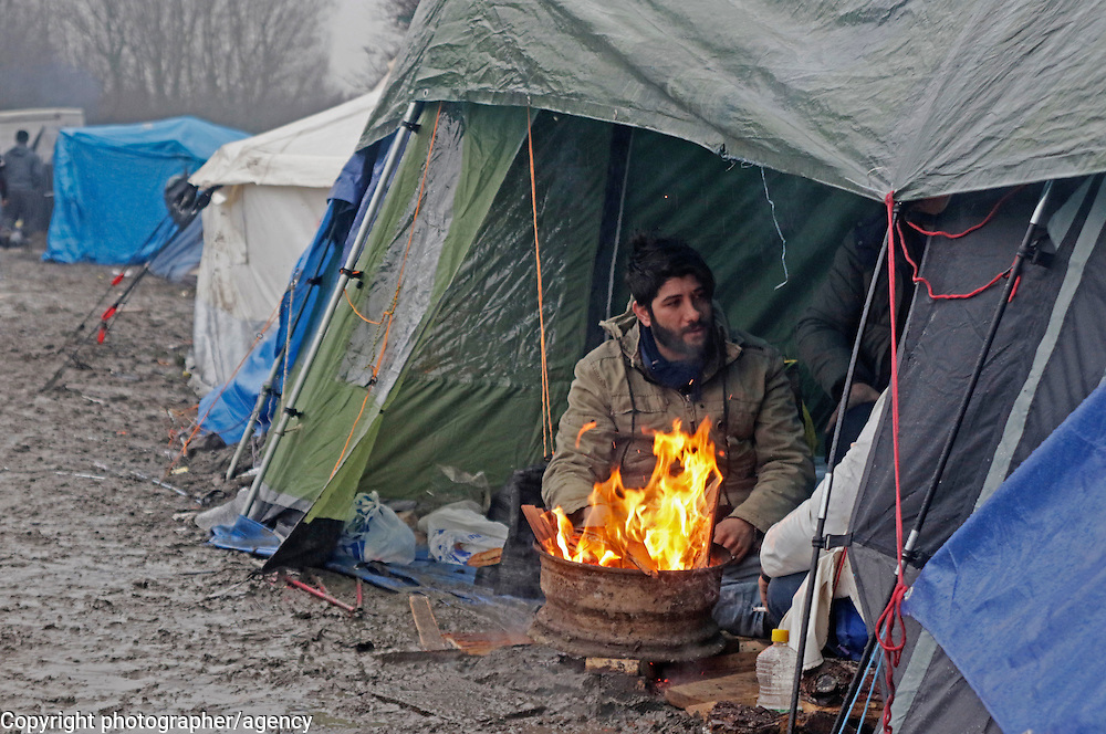 Refugees find shelter 22 January, under a tarpaulin amidst the mud and freezing rain in grande-Synthe refugee camp in northern France.