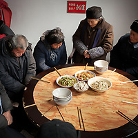 Congregants say grace before a lunch held after a prayer group at a Three-Self Patriotic Movement of the Protestant Church. Just as Protestant churches often serve coffee after Sunday service in the United States, sharing a meal after a service is common in rural Chinese churches.