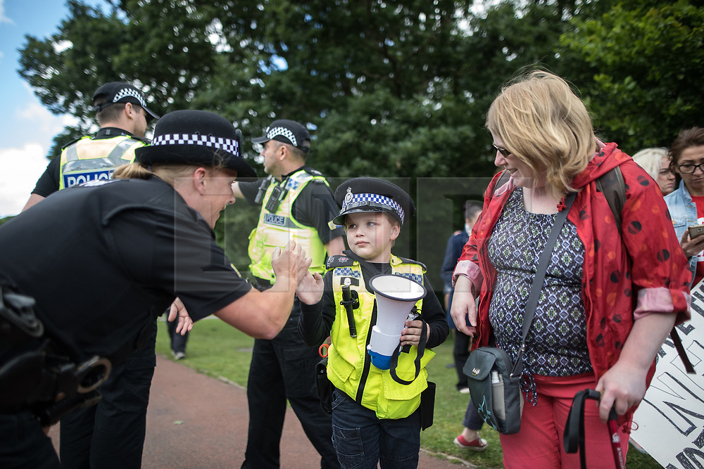 © Licensed to London News Pictures . 07/06/2017. Runcorn , UK. SAMUEL IRVINE (seven) wearing a police dog handler uniform , meets a real policeman at the rally . Labour Party leader Jeremy Corbyn holds a campaign rally in Runcorn, on the final day of the General Election campaign ahead of polls opening tomorrow (8th July 2017) . Photo credit: Joel Goodman/LNP