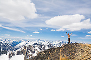 Bare-chested climber Ian Derrington throws his arms into the air in celebration as he stands on the summit of Wallaby Peak, Okanogan National Forest, Washington, looking out into the Cascade Range.