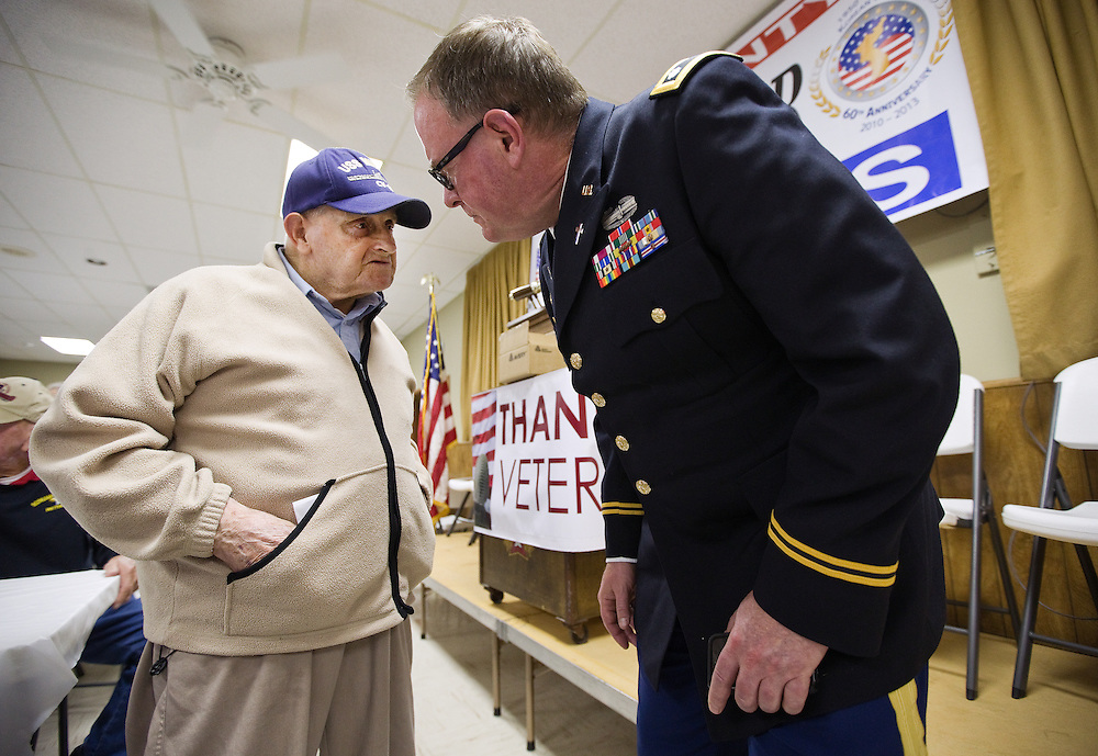 The Rev. Richard Piontkowski, right, leans in a little closer to hear Navy veteran Gerald Engel while the two visit after dinner during a Korean War Veterans Reunion Banquet Wednesday evening at the United Veterans Club in Grand Island. The banquet was in part a fundraiser for the Korean War Hero Flights which are scheduled for early May. (Independent/Matt Dixon)