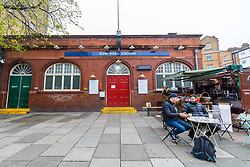 © Licensed to London News Pictures. 19/03/2020. London, UK. Two men drinking coffee outside Bow Road tube station in London which closed this morning. Transport for London (TfL) are closing a number of underground stations from today, as partial closure of the tube and rail network begins in response to the growing coronavirus outbreak in the captial. Photo credit: Vickie Flores/LNP