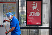 """A placard attached to a bus stop says: """"You must wear a face-covering on Public Transport"""" as a cleaner wearing face protective shield sweeps the fallen leafs nearby Royal Courts of Justice in Central London on Friday, July 24, 2020, as the new rules on wearing masks in England have come into force, with people going to shops, banks and supermarkets now required to wear face coverings. <br /> Authorities said that Police can hand out fines of 100 pounds if people refuse, but authorities are hoping that peer pressure will prompt compliance. (VXP Photo/ Vudi Xhymshiti)"""