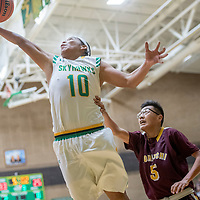 Newcomb Skyhawk Kelkenny Watchman (10) collects a rebound over Tohatchi Cougar Dewayne Begay (5) in the boys District 1-3A championship at Newcomb High School Friday.